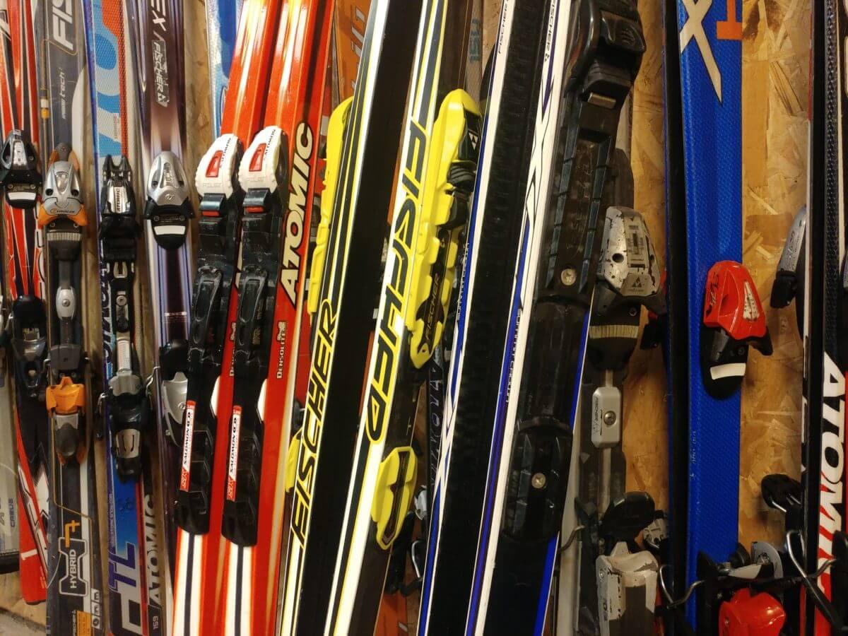 Беговые и горные лыжи стоят у стены